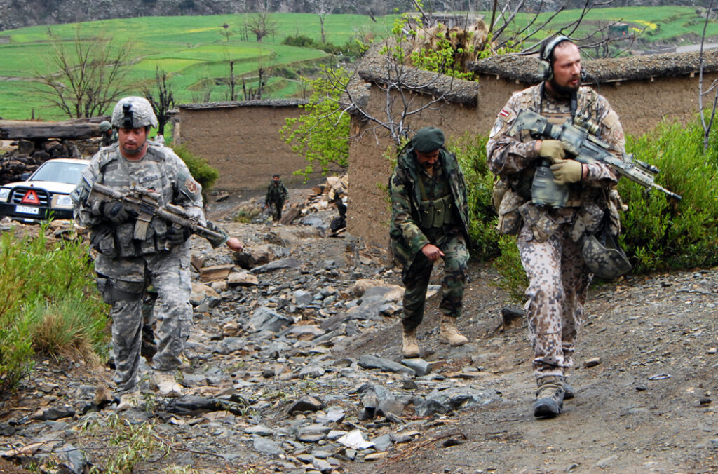 Observer, Mentor, Liaison Team members, Maj. Jim Hickman and Latvian army Maj. Juris Abolins, patrols through the village of Nishagam, in Konar province, Afghanistan alongside members of the Afghan national army, March 18. (U.S. Army photo by Sgt. Matthew Moeller) http://www.nationalguard.mil/news/archives/2009/03/033009-Afghanistan.aspx