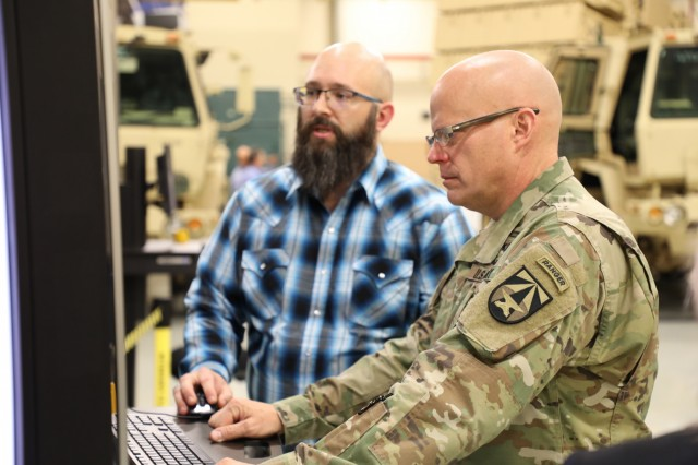 Maj. Gen. John A. George, commanding general of the U.S. Army Combat Capabilities Development Command, learns about metrology from Ben Thomason, left, at the CCDC Aviation & Missile Center Prototype Integration Facility.