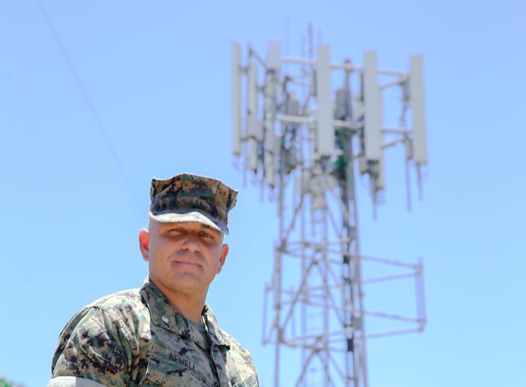 1. Lt. Col. Brandon Newell, Director of Technology and Partnerships for the Marine Corps Installation Next program poses in front of the new 5G tower installed by Verizon at MCAS Miramar on July 15, 2020. The new partnership between MCAS Miramar, Naval Information Warfare Center (NIWC), and Verizon will be a step forward in the Installation Next plan. (U.s. Marine Corps Photo by lance Cpl. Taylor Bidon)